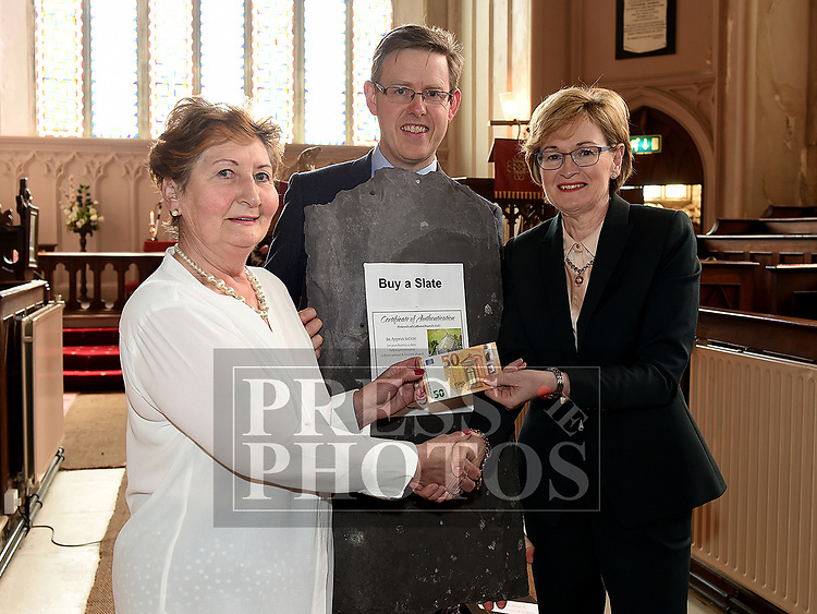 Seamus Roe, Chairperson of Meeting holda a roof slate as Mairead McGuinness MEP pays her Fifty Euro to board member Hazel O'Donohue at the Save the Church launch in Collon Church of Ireland. Photo:Colin Bell/pressphotos.ie