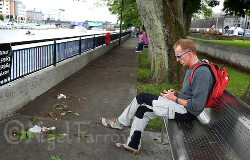 02 JUL 2010 - ATHLONE, IRL - Commentator Peter Jack finds a quiet location by the river to deal with texts before the start of the European Triathlon Championships (PHOTO (C) NIGEL FARROW)