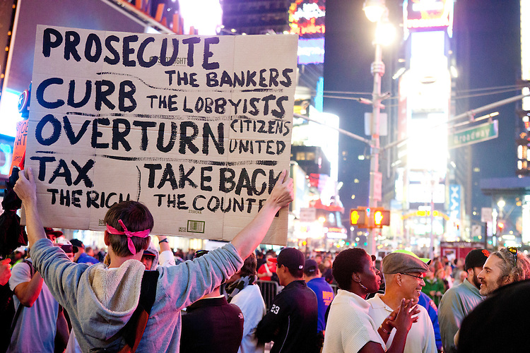 """Protesters with """"Occupy Wall Street"""" in Times Square on October 15, 2011 in New York City.  While crowd estimates numbered in the tens of thousands, police tactics (including nets, motor scooters, barricades, arrests, and intimidation by riders on horseback) prevented the crowd, which had been split up, from joining together as one in the middle of Times Square."""