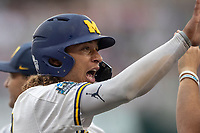 Michigan Wolverines outfielder Jordan Brewer (22) celebrates after scoring a run during Game 1 of the NCAA College World Series against the Texas Tech Red Raiders on June 15, 2019 at TD Ameritrade Park in Omaha, Nebraska. Michigan defeated Texas Tech 5-3. (Andrew Woolley/Four Seam Images)