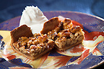 Scrumptious Nut Tart with whipped cream waiting for a fork.  Gorgeous on gold trimmed Goldfish pattern tableware and blue tablecloth