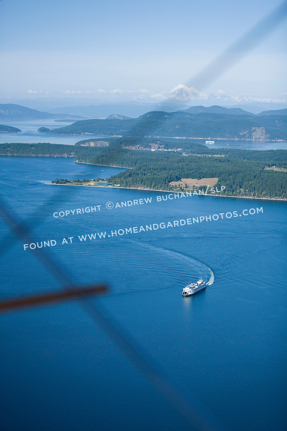 Two white Washington State car ferries makes its way through the deep blue summer waters of the San Juan Islands as seen from the air through the wire cross-braces of a classic biplane.  Snow-capped Mt. Baker rises in the distance.
