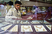 Reflection of pedestrians is seen as a vendor is seen sitting in his Jewellery store in Old Delhi, India. Photo: Sanjit Das/Panos Pictures