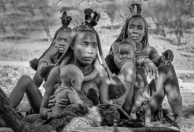 These Himba women and children live in a village in Kaokoland, near Epupa Falls on the Angola border in northern Namibia.  They coat their skin with a mixture of butterfat and ochre, producing a satin reddish sheen.  The region is one of the wildest and least populated areas of the country. Approximately 5,000 Himba inhabit the region.