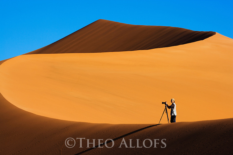 Photographer on sand dune at Sossusvlei in Namib Desert, Namibia