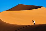Photographer on sand dune at Sossusvlei in Namib Desert, Namibia