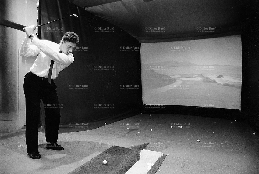 Switzerland. Geneva. A businessman, dressed with a suit and tie, practises indoor golf. He hits the ball into a large movie screen. Model Released © 1988 Didier Ruef