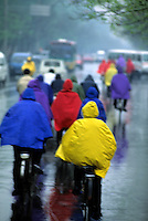 Colorful graphic image of bikers riding bikes in rain with colorful slickers in Beijing China streets artist look as painter