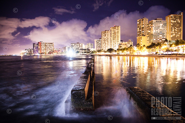 From the edge of Waikiki, O'ahu, a view of waves crashing against a sea breaker, with most of the major hotels and Waikiki Beach in the distance.