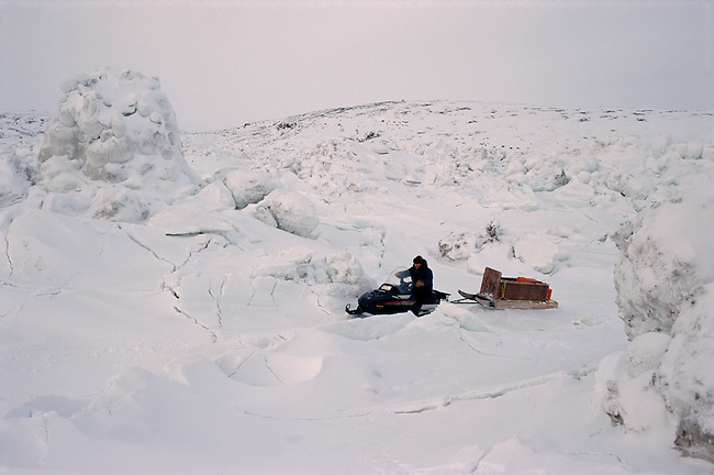 An Inuit hunter drives his snowmobile through rough tidal ice near George River. Ungava Bay, N.Quebec, Nunavik, Canada
