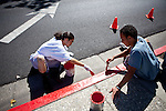 Victor Miller, left, and Shane Marks paint a curb in Stockton, Calif., July 11, 2012. The bankrupt city has cut back on many services, while residents and private contractors are picking up the slack.