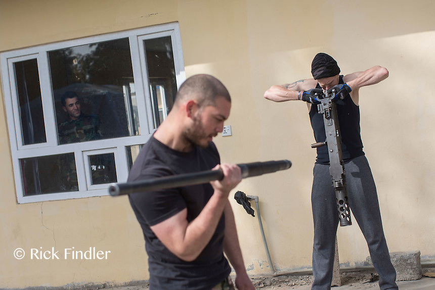 """KURDISTAN, NORTHERN IRAQ, Dokuk.<br /> Qalubna Ma'Kum Feature:<br /> Qalubna Ma'kum (meaning """"Our hearts are With You"""") are a group of foreign volunteer fighters who have joined up with the Peshmerga in Kurdistan to help with the battle against Daesh, also known as ISIS. <br /> <br /> Pictured: A member of the peshmerga watches on through a window as volunteers train and exercise with gun barrels."""