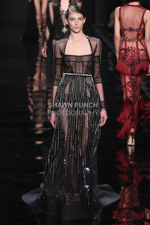 """Model walks runway in a black lace long sleeve bodysuit with embroidered overly skirt from the Reem Acra Fall 2016 """"The Secret World of The Femme Fatale"""" collection, at NYFW: The Shows Fall 2016, during New York Fashion Week Fall 2016."""