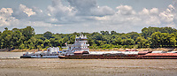 A large barge traveling down the Mississippi River at the Helena West-Helena River Park in Helena Arkansas.