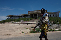 A young man passes in front of the former Somali parliament, destroyed in the early 90s, in northern Mogadishu, Somalia on tuesday November 21 2006..Mogadishu, after 15 years of anarchy is now under the strong fist of the supreme Islamic Courts. Islamist militias are patrolling the streets keeping the city gun less.