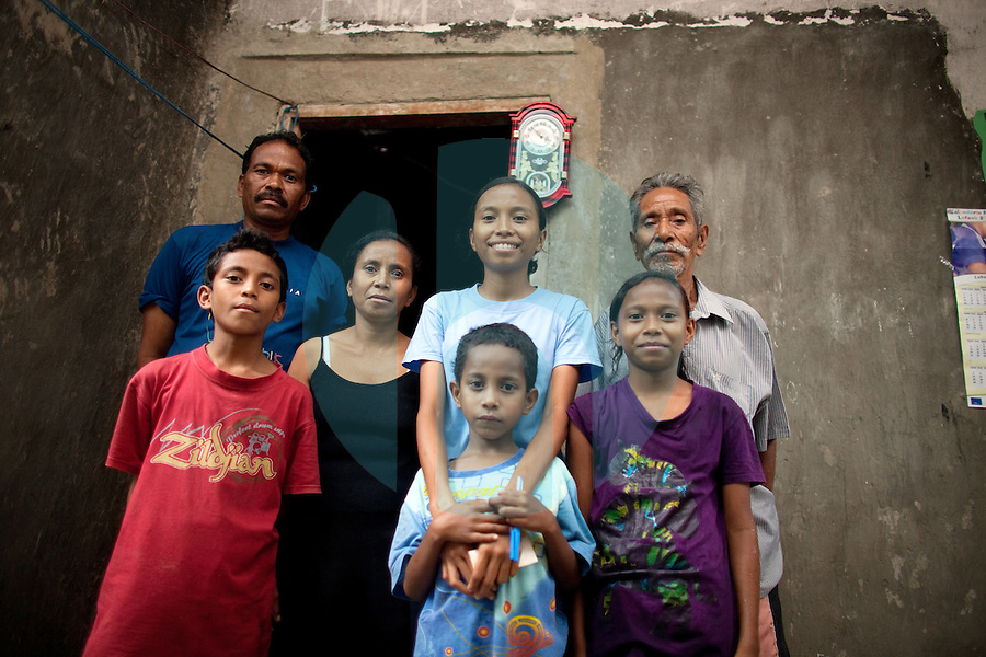 March 15th, 2009_DILI, TIMOR-LESTE_ 18 year old Berta Antonieta Pereira (blue shirt) posses with her family for a photograph in the burnt out remains of her home, which was destroyed during violent clashes in Timor in 2006 near the Timorese capital city of Dili.  Berta was one of four students chosen this year by the Blair Forester Memorial Trust for an overseas scholarship award.  Photographer: Daniel J. Groshong/Tayo Photo Group