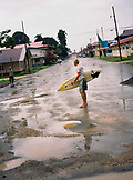 PANAMA, Bocas del Toro, a surfer walks through the middle of town in the rain, Central America