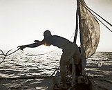 MADAGASCAR, Anjajavy, fisherman in pirogue throwing a rope at dusk