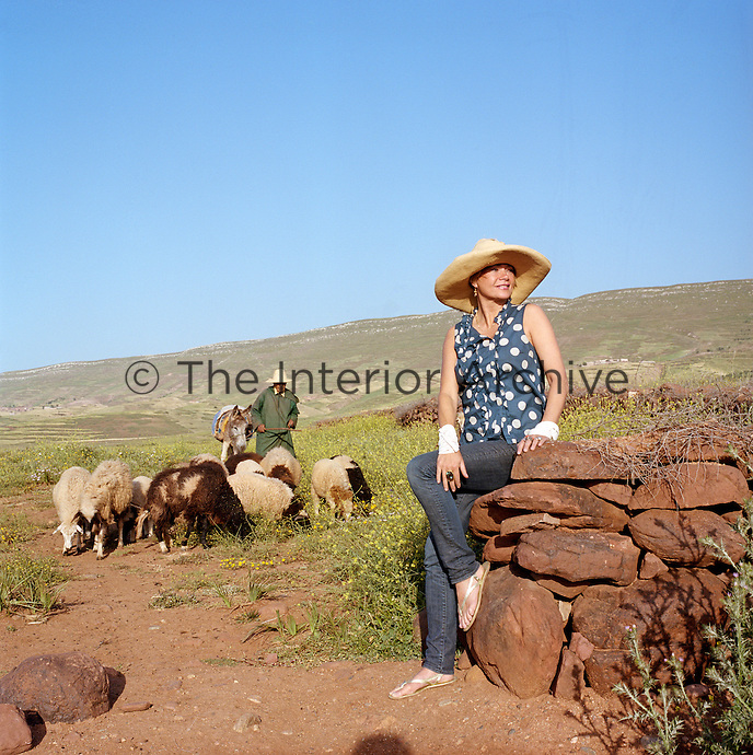 A shepherd brings his small flock of sheep down off the hill while fashion designer Liza Bruce admires the view