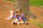 Toddler playing with four doll babes under pine tree.