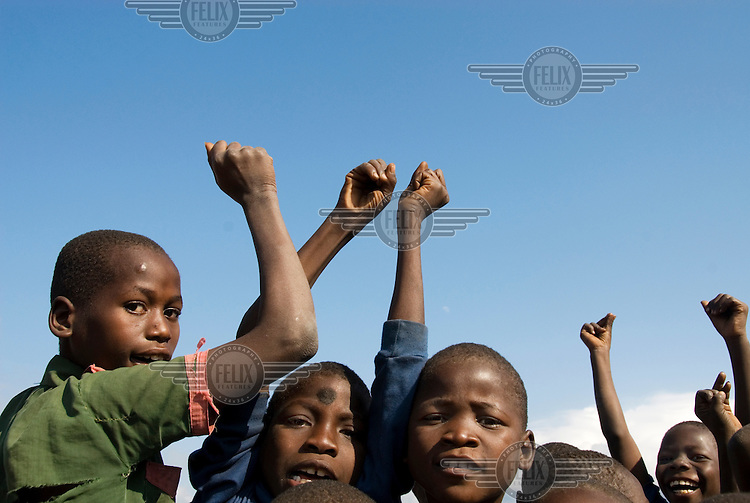 Standard 1 pupils hold their hands up as they play at breaktime at Mchere primary school.