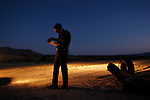 U.S. Border Patrol Agent Thomas Steel writes a report after apprehending five illegal aliens in the desert near El Centro, Calif. on Wednesday, March 30, 2005.<br />