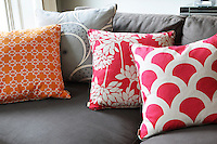 Detail of a variety of patterned cushion covers  in shades of orange, red and pink