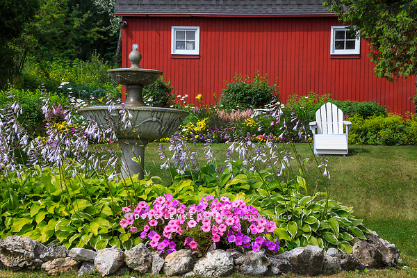 An adirondack chair in the flower garden by the red barn on Mackinac Island, Michigan, USA