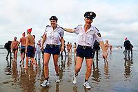 Traditionele Nieuwjaarsduik in Scheveningen. Mensen zijn verkleed als politie agenten in korte broek