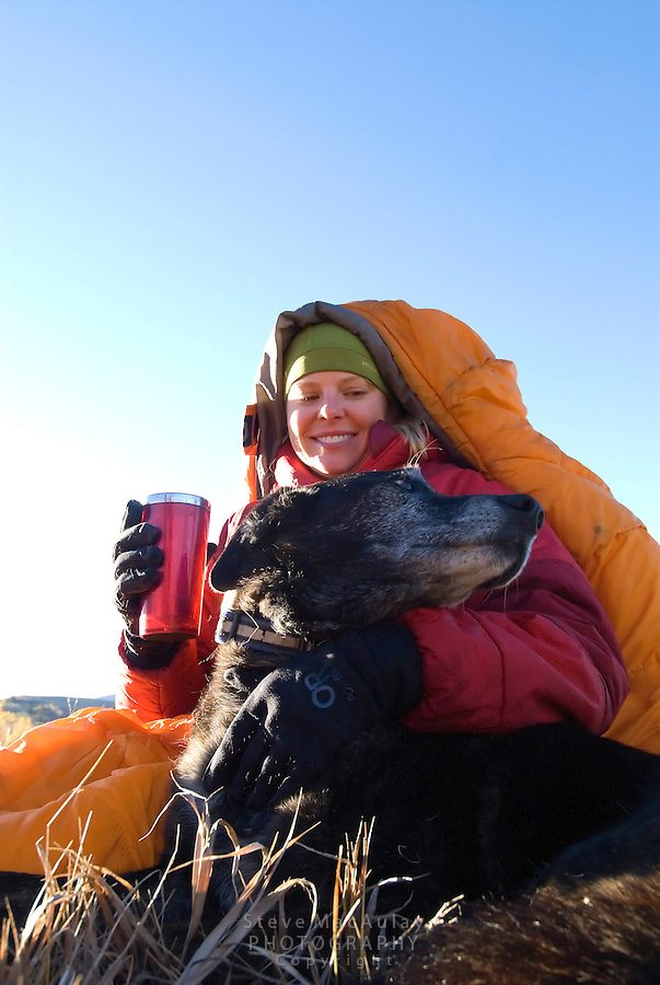 Young woman wrapped up in orange sleeping bag, holding coffee mug and petting dog, at sunrise at campsite, Fall, Grand Teton National Park, Wyoming