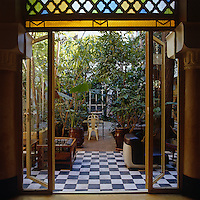 A pair of glass doors open out onto a shady courtyard scattered with classic 20th century pieces of furniture