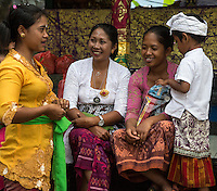 Jatiluwih, Bali, Indonesia.  Three Balinese Women Talking,  Luhur Bhujangga Waisnawa Hindu Temple.  Little Boy in Sarong and Udeng, the traditional male head wrap.