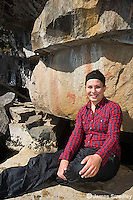 Young woman sitting in front of a rock with pictographs.