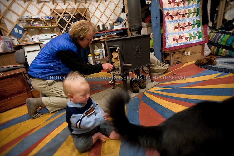 12/12/2009--Seldovia, Alaska, USA..Bretwood Higman (left),with his son Katmai, throws wood in the heater in the morning in their yurt in Seldovia, Alaska...The yurt is made by Nomad Shelter in Homer, Alaska, and cost about $14,000. Bretwood Higman ('Hig'), 33 and Erin McKittrick, 30, built it in November, 2008 on land owned by Hig's mother in Seldovia.The yurt is 24' in diameter, the ceiling is over 12' in the middle, 7' around the edge. It has no running water but does have electricity and internet access...McKittrick grew up in Seattle and met Higman, from Seldovia, at Carleton College in 2001. In June 2007, the couple left Seattle for the Aleutian Islands, traveling 4000 miles solely by human power through some of the most rugged terrain in the world; their adventure has recently been published in a book written by McKittrick with Hig's photographs titled, 'A Long Trek Home: 4,000 Miles by Boot, Raft, and Ski'...Together, the couple also run a small environmental non-profit, Ground Truth Trekking, which uses trekking to explore the complexities of natural resource issues. The couple lives with their 10 month old son son, Katmai, in Seldovia, Alaska, a 300 person village just off the end of the road system...©2009 Stuart Isett. All rights reserved.
