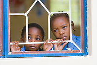 Children look through a classroom school window in the small village of Usa River, Tanzania, East Africa