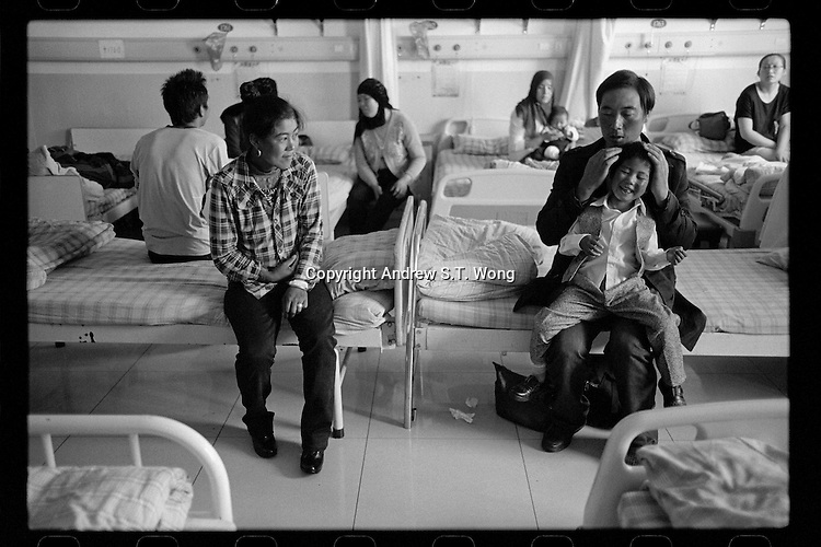 A Tibetan couple plays with their daughter before her cleft palate operation organized by Smile Angel Foundation at a hospital in Xining, Qinghai province, China, August 2013. (Names withheld for privacy)