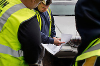 John Mullaney (center), temporary supervisor for construction for the Boston Public Works Department, and David Dollosa look at a printout showing a member of the public's complaint about specific road or sidewalk conditions in Boston, Massachusetts, USA, on April 12, 2012.  The city uses a computer system to track public complaints and record work done by city crews to mitigate these complaints.  A supervisor or inspector photographs before and after pictures of the work in addition to making notes about the work done.
