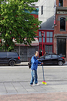 Elderly Chines man carrying a colorful broom in Chinatown, Vancouver, BC, Canada