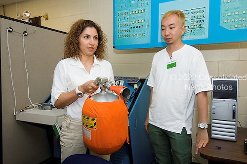 Houston, TX - July 12, 2006 -- Daisuke Enomoto (right) and Anousheh Ansari, primary and backup spaceflight participants, respectively, for the ISS Soyuz 13 (TMA-9) mission to the International Space Station, participate in a training session in the Space Vehicle Mockup Facility at Johnson Space Center. The spaceflight participant will launch with Expedition 14 and land with Expedition 13 under a commercial contract with the Russian Federal Space Agency..Credit: NASA via CNP