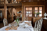 A dining table and chairs occupy part of the open living/dining/kitchen area on the first floor of the chalet
