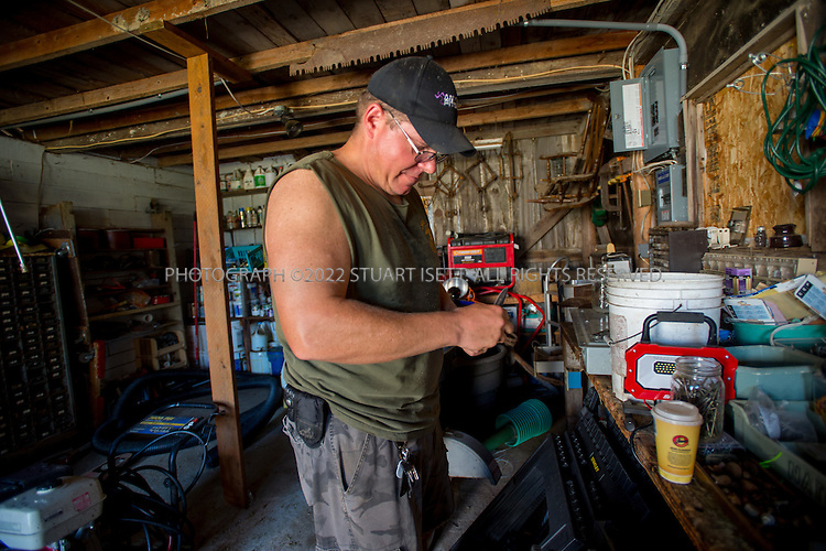8/12/2016-- Mount Vernon, WA, USA<br /> <br /> Staff from the Schultz Family Foundation visit the Growing Veterans farm in Mt. Vernon, Washington, about an hour north of Seattle.<br /> <br /> <br /> Here, veteran Andrew Meyer works in the farm's tool shed.<br /> <br /> From http://growingveterans.org:<br /> <br /> &ldquo;Since 2012, Growing Veterans has been combining veteran reintegration with sustainable agriculture. Our unique model addresses the growing desire for alternative therapies for Post-Traumatic Stress (PTS) and Traumatic Brain Injury (TBI), as well as suicide prevention through peer-support and Applied Suicide Intervention Skills Training (ASIST) certification. We encourage continued service through volunteerism, and collective impact through collaboration with other local, regional, and national stakeholders.&nbsp; We provide opportunities for vets in transition to develop their resumes and identify how to translate skills learned in the military to new roles in the civilian sector. Further, our vets serve as leaders in the important movement toward sustainable agriculture&rdquo;<br /> <br /> Photograph by Stuart Isett. &copy;2016 Stuart Isett. All rights reserved.
