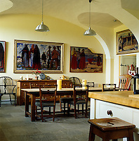 The kitchen/dining room features a stone-flagged floor, a vaulted ceiling and a triptych on the wall