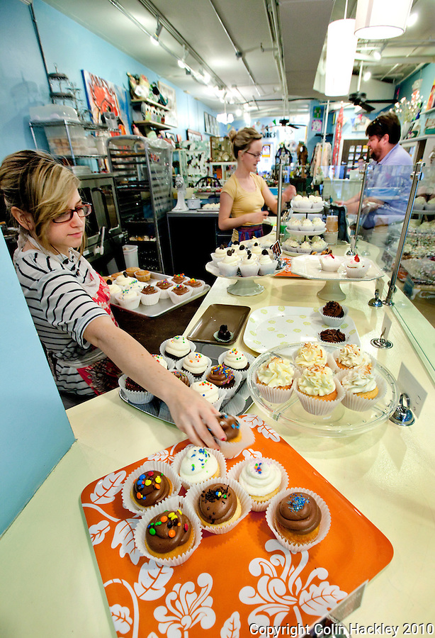 TALLAHASSEE, FLA. 8/19/10-VISITTALLY-081910-HACKLEY-Annalise Mabe slides some fresh goods onto the tray at Lucy & Leo's Cupcakery in Tallahassee...COLIN HACKLEY PHOTO