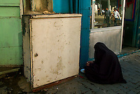 Baghdad, Iraq, Feb 23, 2003.A woman beggar eating a frugal meal on the sidewalk in front of a small restaurant in central Baghdad. Many war widows have no better alternative than to live in the streets.