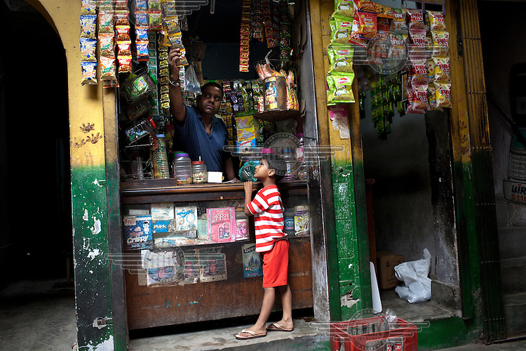 A child buys confectionary from a stall at a local market place in Wazirpur village in Ashok Vihar in New Delhi.