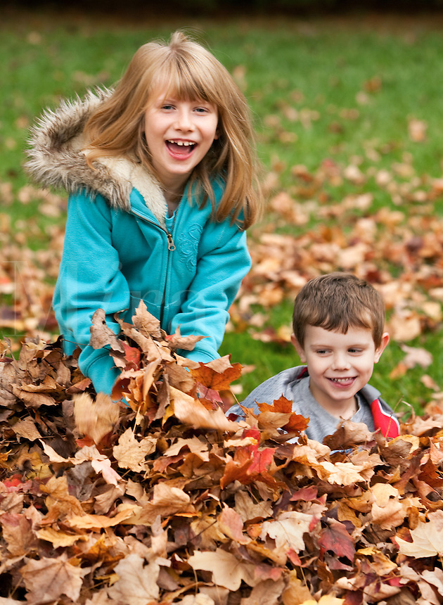 Brother and sister playing in fall leaves