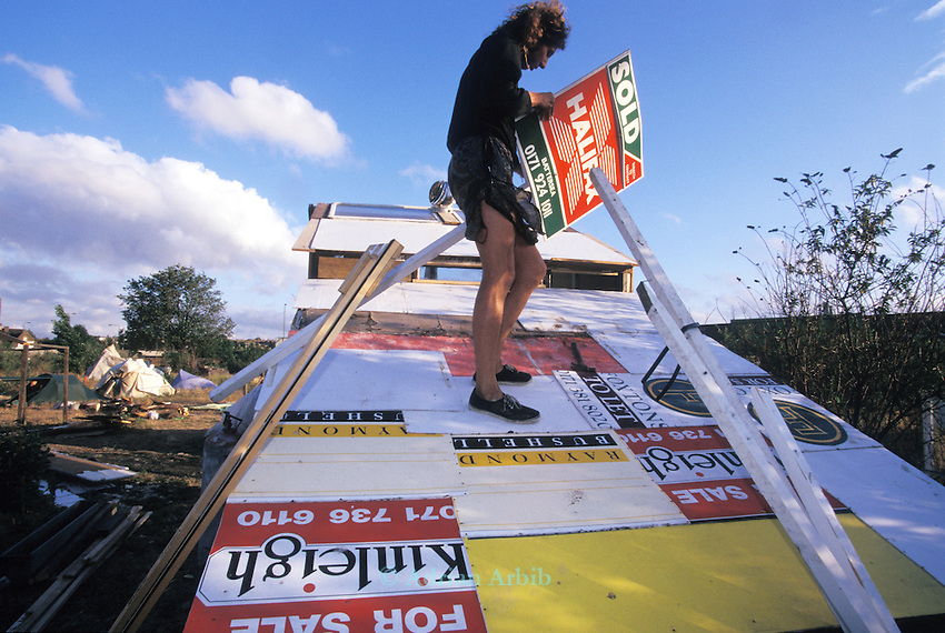 Dave using estate agents signs to tile his house on the site of the Wandsworth Eco village.