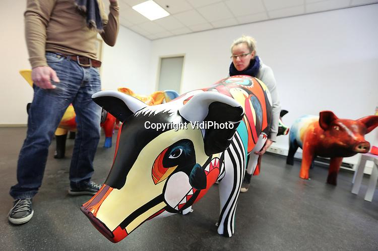 Foto: VidiPhoto<br /> <br /> VEGHEL - Kunstenaars leggen in een leegstand kantoorpand in het Brabantse Veghel dinsdag de laatste hand aan twintig zogenoemde designpigs. De polyester varkensmodellen krijgen een artistiek uiterlijk en hebben als doel de varkenssector een positief imago te geven. Het geld wat de kunstwerken opbrengen komt ten goed aan het Leontienhuis in oprichting, waar meisjes met een eetprobleem worden opgevangen. Vanaf woensdag verhuizen de eerste varkens naar hun nieuwe eigenaar, vooral bedrijven die gerelateerd zijn aan de varkenssector. Volgens initiatiefnemer en veevoederfabrikant Huub Fransen kunnen ook particulieren een kunstwerk aanschaffen. De kosten bedragen 5000 euro per varken. Het tiental internationale kunstenaars dat de modellen op diverse plekken in Nederland op openbare plekken beschildert, krijgt alleen de kosten vergoed. Designpigs probeert op deze wijze een andere beeld te cre&euml;ren van de varkenssector. &quot;We krijgen vaak veel onterecht commentaar. Mensen luisteren liever naar het eenzijdige beeld van de Partij voor de Dieren, dan naar mensen uit de praktijk. En of je nu van varkens houdt of niet, deze designpigs zijn gewoon mooi&quot;, aldus Fransen.  De organisatie heeft plannen om deze zomer door het land te gaan toeren met de kunstvarkens en om bovendien &quot;goedkopere&quot; beschilderde kunstbiggen te gaan verkopen. Staatssecretaris Sharon Dijksma heeft inmiddels al een beschilderd varken aangeboden gekregen voor haar ministerie. Fransen: &quot;Uiteindelijk hebben we graag dat heel Nederland een kunstvarken in huis neerzet.&quot;