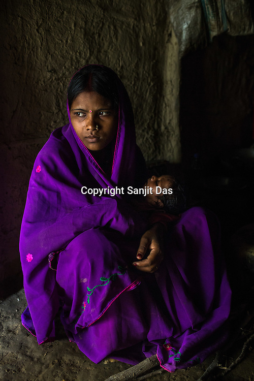 16 year old Lal Chuni Devi holds Srikanthi Devi's 3 months old son, Chandan Kumar in her house in Ramgarwa village in Raxaul district in Bihar, India.