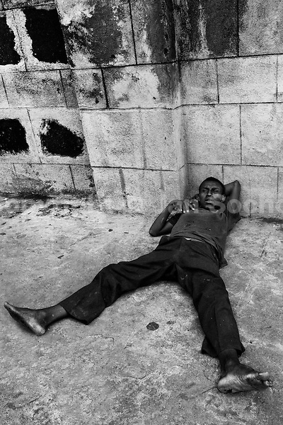 A young Nicaraguan boy got high by sniffing the shoe glue on the street of Managua, Nicaragua, 5 November 2004. Hundreds of kids struggle on the streets of Managua, sniffing glue to avoid hunger and get out of the misery. The glue is the cheapest drug available in every slum in Latin America. It is widely sold to the kids because there is no government control, neither restriction. The police can not intervene because the glue is not legally considered as a drug. Many sniffers end up with permanent brain damage, their motion ability is reduced, some of them keep in unstoppable tremor till the end of the life.
